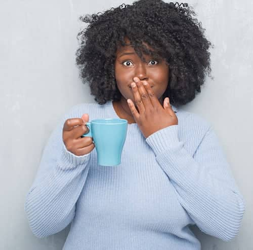 Lady covering her mouth while holding a cup of coffee